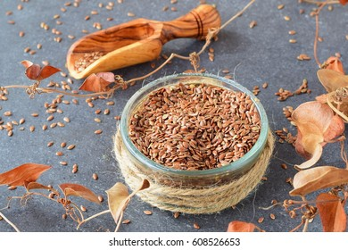 A glass bowl with flax seeds, olive wood scoop, dry leaves on a grey abstract background. Healthy eating concept , dieting, beauty.