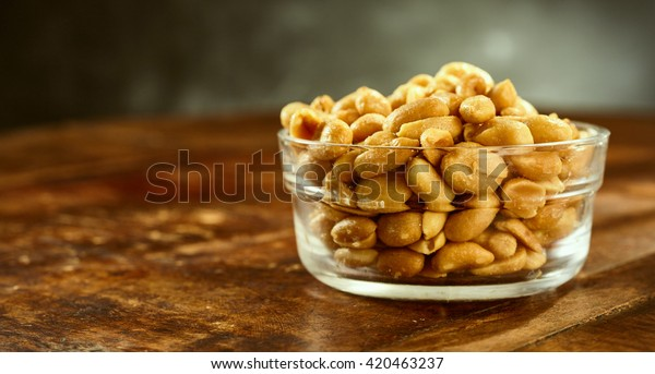 Glass bowl of fresh roasted salted peanuts or groundnuts on an old wooden table or bar counter in a side view with copy space