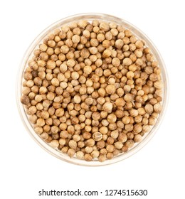 Glass bowl full of coriander seeds isolated on a white background viewed from direclty above.