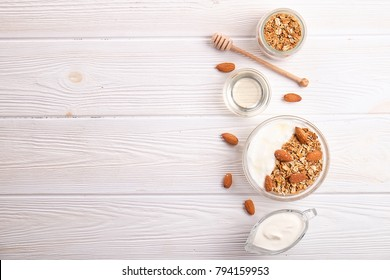 Glass bowl with Greek yogurt and mixed nuts. Healthy sports vegetarian protein rich diet, homemade granola breakfast with milk, almond, cashew, hazelnut, rolled oats. Top view, background, copy space