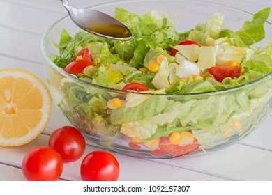 A glass bowl with green salad, cherry tomatoes and corn. A spoon with olive oil.