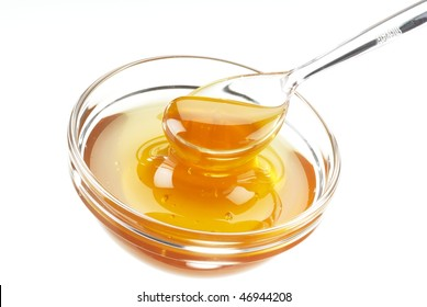 glass bowl with honey an a transparent spoon