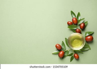 Glass bowl with jojoba oil and seeds on green background, flat lay. Space for text