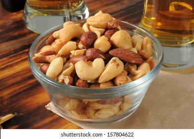 A glass bowl of mixed nuts on a bar counter with beer