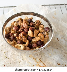 Glass bowl of mixed nuts on parchment paper and cooling rack
