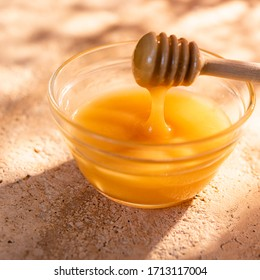 A glass bowl of natural raw honey in the morning of a sunny day