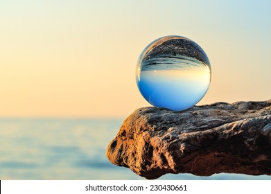 Glass bowl on the boulder at the sea