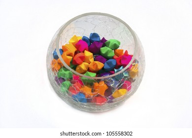 A glass bowl of paper origami stars of different colors with white background