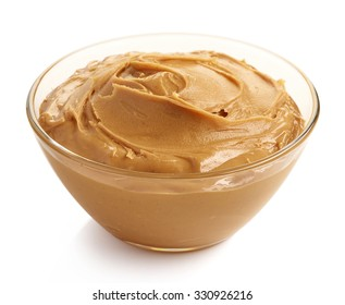 Glass bowl of peanut butter isolated on white background