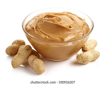 Glass bowl of peanut butter with peanuts isolated on white background