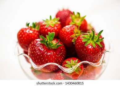 Glass bowl with red, delicious, strawberries against a whitebackground.  Short dept of field with the front strawberries in focus.