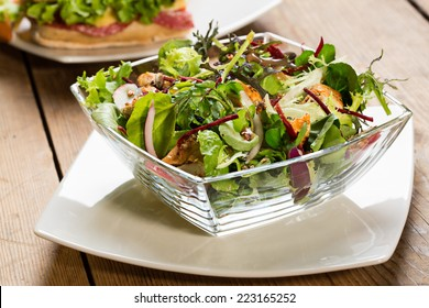 Glass bowl of salad with lettuce, tomatoes, cheese, red onions and pieces of chicken. Placed on a white square plate on a wooden table.