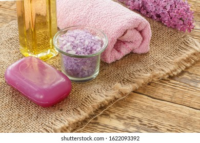 Glass bowl with sea salt, soap, bottle of oil, lilac flowers and towel for bathroom procedures on sackcloth and wooden boards. Spa products and accessories. Top view.
