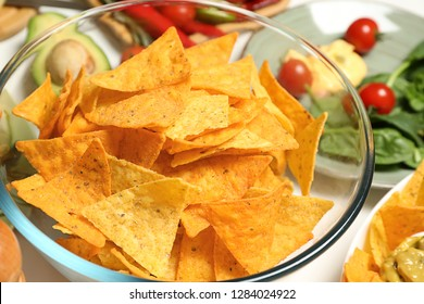 Glass bowl with tasty corn chips on table, closeup