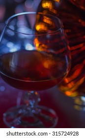 The glass of brandy and bottle.  Back light.