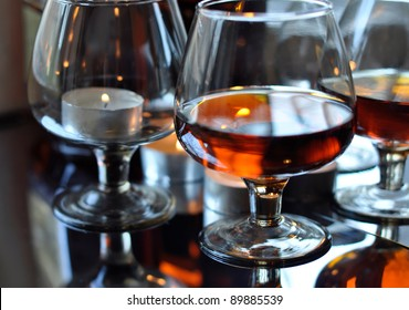 a glass of brandy and a candle, reflection