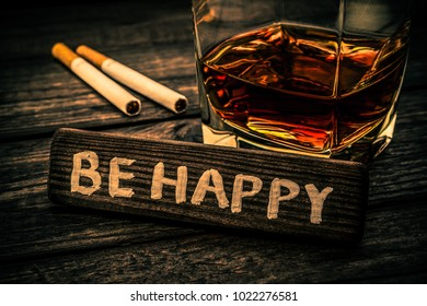 """Glass of brandy with cigarettes and the wooden plank on it is an inscription """"BE HAPPY"""" on an old wooden table. Close up view, focus on the inscription, image vignetting and the orange-blue toning"""