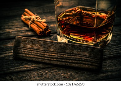 Glass of brandy with cinnamon sticks tied with jute rope and the empty wooden plank on an old wooden table. Close up view, focus on the wooden plank, image vignetting and the orange-blue toning