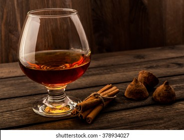 Glass of brandy and a couple of chocolate truffles with cinnamon sticks tied with jute rope on an old wooden table. Focus on the glass of brandy