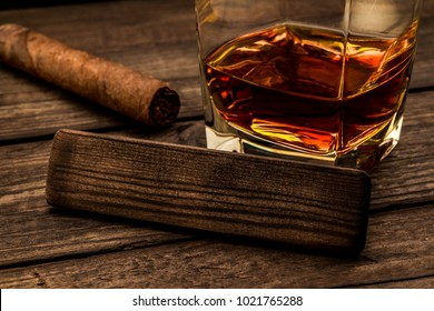 Glass of brandy with cuban cigar and the empty wooden plank on an old wooden table. Close up view, focus on the wooden plank