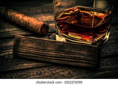 Glass of brandy with cuban cigar and the empty wooden plank on an old wooden table. Close up view, focus on the wooden plank, image vignetting and the orange-blue toning