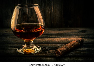 Glass of brandy and cuban cigar on a wooden table. Focus on the cuban cigar, angle view, image vignetting and the orange-blue toning