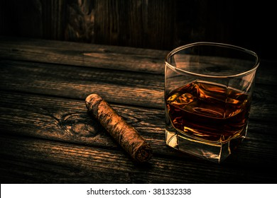 Glass of brandy and cuban cigar on an old wooden table. Angle view, image vignetting and the orange-blue toning
