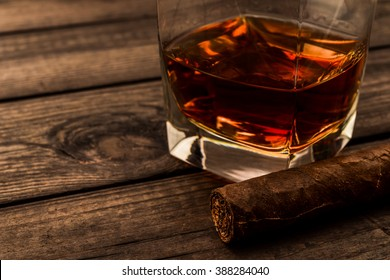 Glass of brandy and cuban cigar on an old wooden table. Close up view, focus on the cuban cigar