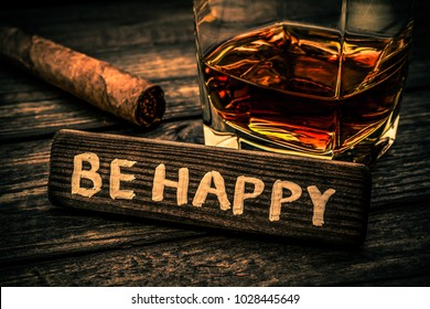 """Glass of brandy with cuban cigar and the wooden plank on it is an inscription """"BE HAPPY"""" on an old wooden table. Close up view, focus on the inscription, image vignetting and the orange-blue toning"""