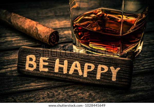 ブランデーにキューバの葉巻と木の板は、古い木のテーブルの上に「BE HAPPY」と書かれている。接写ビュー、碑文、画像のぼかし、オレンジと青の調色にフォーカスを当てる