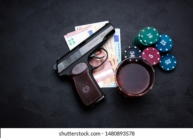 A glass of brandy and a few piles of casino chips next to a pile of euros on which lies a Russian gun