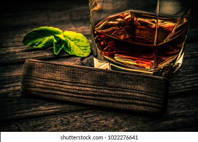 Glass of brandy with mint sprig and the empty wooden plank on an old wooden table. Close up view, focus on the wooden plank, image vignetting and the orange-blue toning