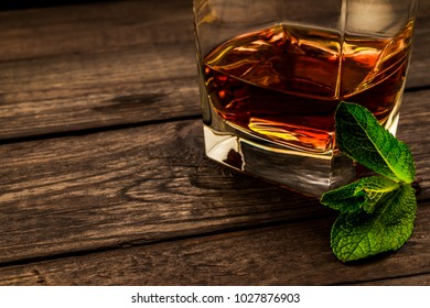 Glass of brandy with mint sprig on an old wooden table. Close up view