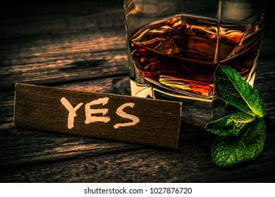 """Glass of brandy with mint sprig and the wooden plank on it is an inscription """"YES"""" on an old wooden table. Close up view, focus on the inscription, image vignetting and the orange-blue toning"""