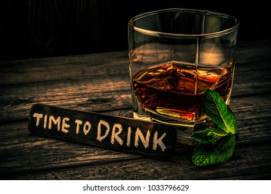 """Glass of brandy with mint sprig and the wooden plank on it is an inscription """"time to DRINK"""" on an old wooden table. Angle view, focus on the inscription, image vignetting and the orange-blue toning"""