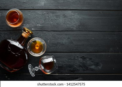 A glass of brandy on a black background. Top view. Free space for your text.