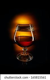 Glass of brandy on black background.