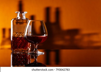 Glass of brandy on a black reflective background in bar.