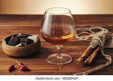 Glass of brandy on a old wooden table with a bowl with chocolate, cinnamon stiks and chili peppers. Warm background.