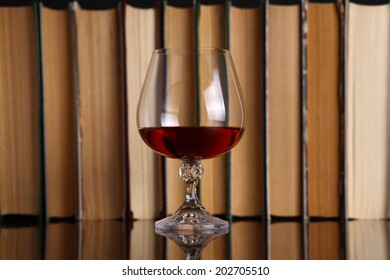 Glass of brandy on a reflective surface with books