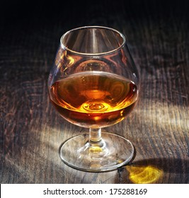 glass of brandy on wooden table