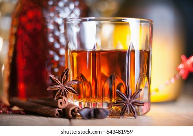 Glass of brandy on the wooden table and spices