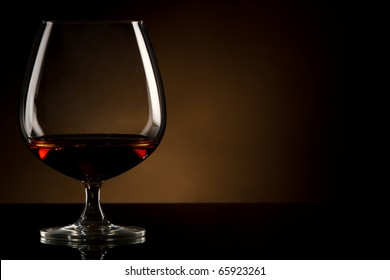 Glass of brandy over brown background