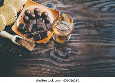 A glass of brandy. Whiskey. Assortment of chocolates on the wooden surface. Top view. Toned effect image