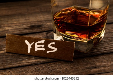 """Glass of brandy with the wooden plank on it is an inscription """"YES"""" on an old wooden table. Close up view, focus on the inscription"""