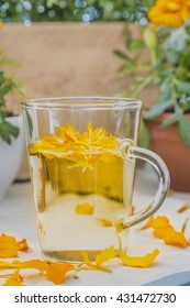 The glass with brew of Tagetes petals on linen tablecloth.