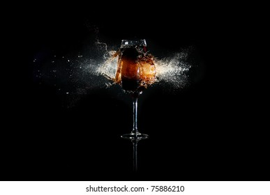 Glass with brown liquid exploded by bullet with many splashes around at the black background