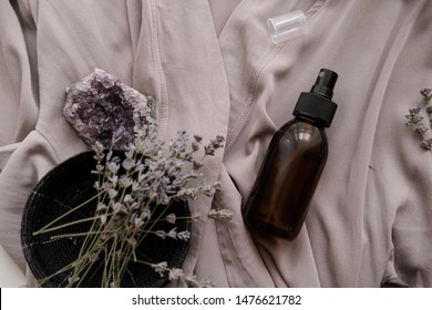 Glass brown spray bottle with organic cosmetics on gray fabric. Beauty blogging concept
