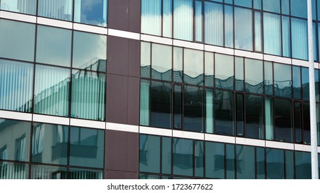 Glass building with blue sky background. Modern office building detail, glass surface clouds reflected in windows of modern office building.