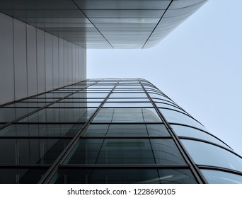 Glass building with geometric shapes seen from below and clear sky
